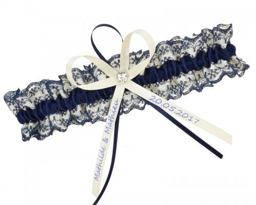 Cette jarretière bleu foncé est en dentelle bleue est décorée de rubans est individualisable.